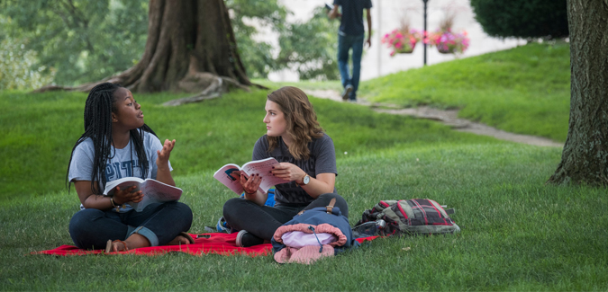 Two girls sitting on a lawn outside on Pitt's campus