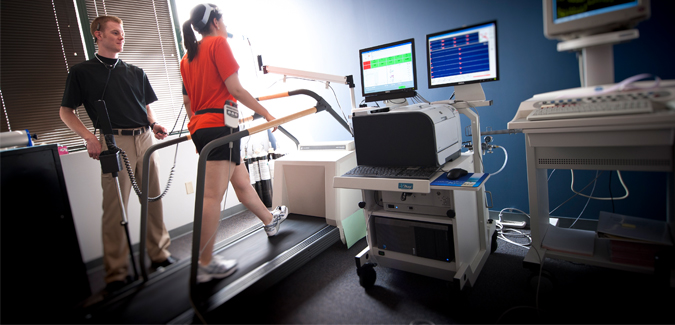 A student measures a person's vitals on a treadmill