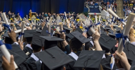 Graduates wave their diplomas in the air at a commencement ceremony