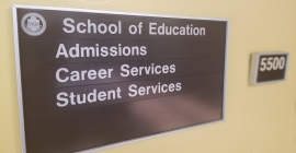 A directional sign within the School of Education at Posvar Hall