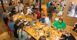 A group of parents, teachers, and students in a Maker lab space