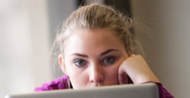 A student looks at her laptop screen