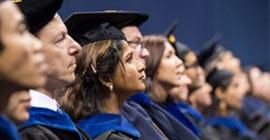 Graduates listen during a commencement ceremony.
