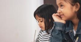Two young children listen to a teacher