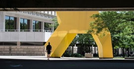 A person walks by Posvar Hall and a large yellow sculpture