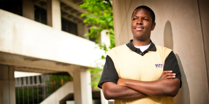 A smiling male student stands outside of Posvar Hall with his arms folded