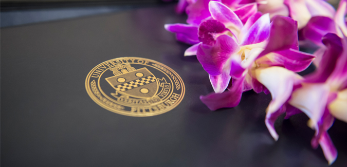 A flower and the University seal engraved on a publication cover
